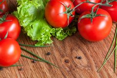 Red tomatoes with green salad on wood Royalty Free Stock Photos