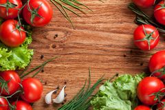 Red tomatoes with green salad on wood Royalty Free Stock Images
