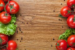 Red tomatoes with green salad on wood Royalty Free Stock Photography