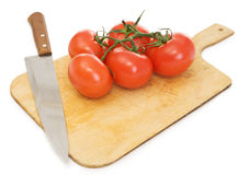 Red tomatoes and kitchen knife on a chopping board Stock Image