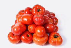 Red tomatoes laid by a pyramid. On a white background Stock Photography