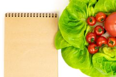 Red tomatoes in lettuce isolated on white background next to Notepad. Composition of red tomatoes in lettuce leaves on a white bac royalty free stock images