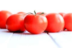 Red tomatoes on a light wooden background stock image
