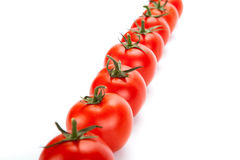 Red tomatoes lined up in a row on a white background Stock Photo