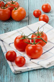 Red tomatoes on a linen napkin. On a turquoise colored wooden surface Stock Images