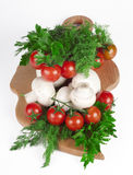 Red tomatoes and mushrooms. On a kitchen board Royalty Free Stock Photos