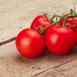 Red tomatoes over wooden table - studio shot Stock Image