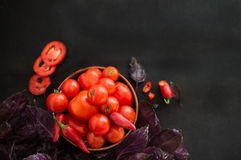 Red tomatoes and pepper in a bowl.  Leaves fresh basil. Ripe red tomatoes and hot pepper in a bowl on a dark background. Leaves of fresh purple basil Royalty Free Stock Photography