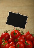 Red tomatoes with price sign over jute canvas. Red ripe fresh small cherry tomatoes with black wooden chalkboard price sign tag close up over jute burlap canvas Royalty Free Stock Images
