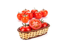 Red tomatoes in a small basket on a white background Royalty Free Stock Photo