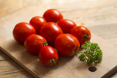 Red tomatoes and a sprig of parsley on a wooden cutting board. Stock Photos