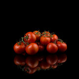 Red tomatoes with stems on dark background. With reflection Royalty Free Stock Images