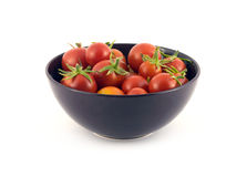 Red tomatoes in violet bowl isolated on white. Still life with red tomatoes in violet bowl isolated on white closeup. Horizontal view Stock Photos