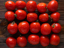 Red tomatoes with water drops. Tomatoes of different varieties. tomatoes background. Stock Photo