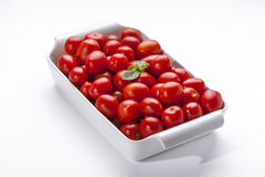 Red Tomatoes. White bowl of red tomatoes over a seamless white background Stock Photo