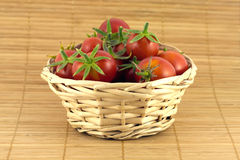 Red tomatoes in wicker basket on straw mat Stock Image