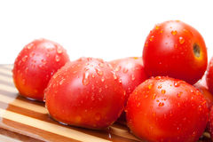 Red tomatoes on a wooden board with water drops Royalty Free Stock Image