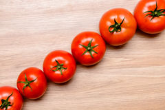 Red tomatoes on wooden ground Royalty Free Stock Photo