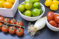 Red tomatoes, yellows, greens and chives Stock Photo