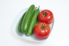 Red tomatos and green cucumbers on a white plate Royalty Free Stock Image