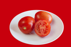 Red-tomatos-on the-white-plate. Two red tomatos and a half on the white plate on the red background Stock Photography