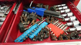 Red Tool box tray old screwdriver bits heads. Red Tool box with mixed tools clamp hammer pliers wrench collection soldering wire hex key cable screwdriver Allen stock photos