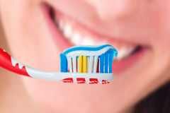Red toothbrush with blue two color toothpaste on human smile. Red toothbrush with blue two color toothpaste with human smile background. Photo of dental hygiene Stock Images