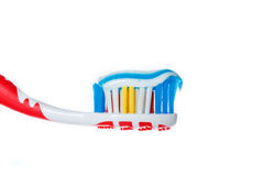 Red toothbrush with blue two color toothpaste on light surface Stock Photos