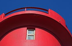 RED TOP OF LIGHTHOUSE AGAINST A BLUE SKY. Close view of a red top of lighthouse against a blue sky Royalty Free Stock Photography