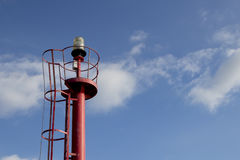 Red top navigation light tower over a blue sky with clouds. Closeup image of the top of a red navigation light tower at the entrance of a sea port Stock Images