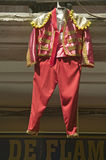Red toreador bull fighting outfit for boy hangs in Centro old district of Sevilla Spain Royalty Free Stock Images