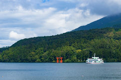Red Torii gate and tourist boat cruising Ashi lake Royalty Free Stock Photo