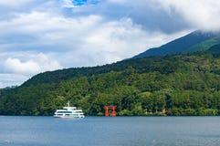 Red Torii gate and tourist boat cruising Ashi lake Royalty Free Stock Image