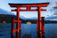 Red torii gate in Hakone, Japan. Red torii gate and tourist boat sailing in Lake Ashi at dusk, Hakone, Japan stock photo