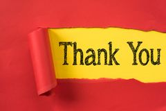 Red torn paper revealing THANK YOU word on yellow paper stock photos
