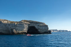 Red tour boat passing cave in white cliffs at Bonifacio Stock Photography