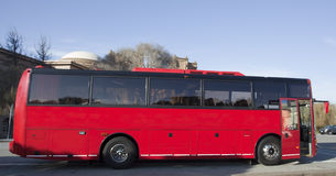 Red Tour Charter Bus. Side view of parked red tour charter bus with open door Royalty Free Stock Image