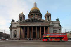 Red tourist bus drives past St. Isaac`s Cathedral. Royalty Free Stock Photography