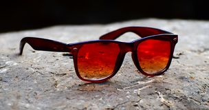 Red tourist sunglass on a soil surface photograph. A beautiful red coloured tourist sunglass kept on a soil made surface stock photograph Royalty Free Stock Image