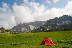 Red tourist tent is against mountains Stock Images
