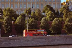 A red touristic double decker bus drives along Moscow Kremlin royalty free stock photo