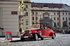 Red touristic oldtimer from the beginning of the 20th century on the historic cobbled road in Prague Stock Images