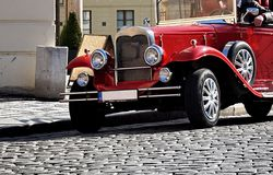 Red touristic oldtimer from the beginning of the 20th century on the historic cobbled road in Prague Royalty Free Stock Photography