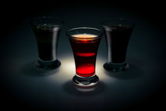 Red and tow shot glass on a dark background in the spot light Royalty Free Stock Photos