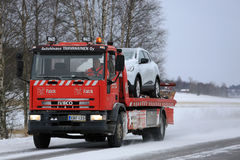 Red Tow Truck Tows a Breakdown Car in Winter Royalty Free Stock Image