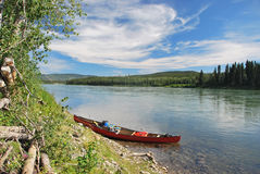 Red towed and abandoned canoe on Yukon River. In Canada Royalty Free Stock Photo