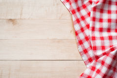 Red towel over wooden kitchen table Royalty Free Stock Photos