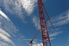 Red Tower crane against a blue sky Stock Image
