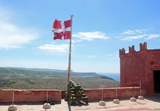 On the Red Tower, Malta, with canon and Maltese flag Royalty Free Stock Images