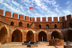 Red tower of red brick with a Turkish flag and the blue sky. Stock Photo